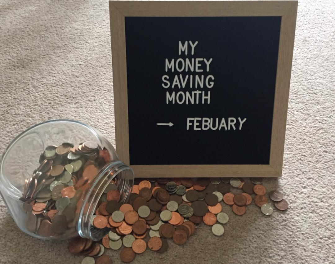 My Money Saving Month February Written on a letter board with coins spilling from a jar