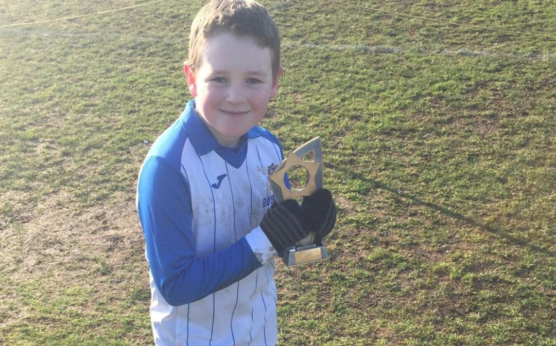 Boy holding football trophy