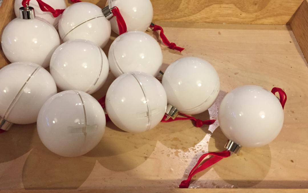 Preparing the baubles by painting them white