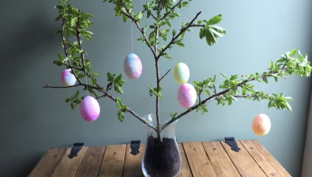 Tissue paper dyed eggs displayed on a tree branch