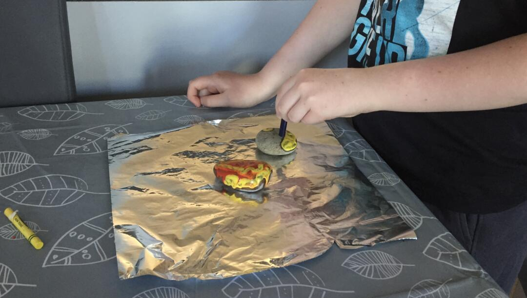 The crayon melting on contact with the hot rock