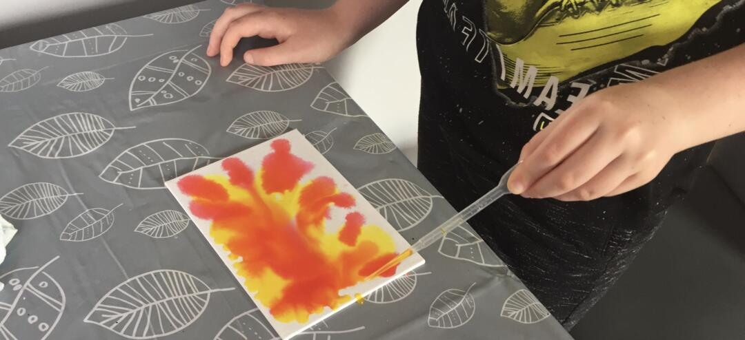 Adding food colouring to the wet surface using a dropper