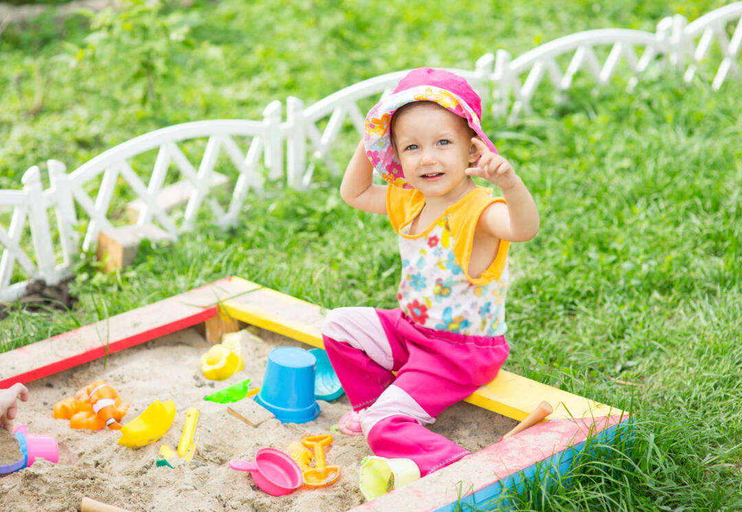 Toddler playing with outside toy sandpit