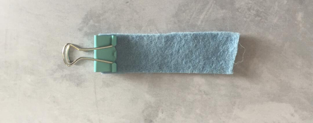 Putting one end of the felt in the foldback clip