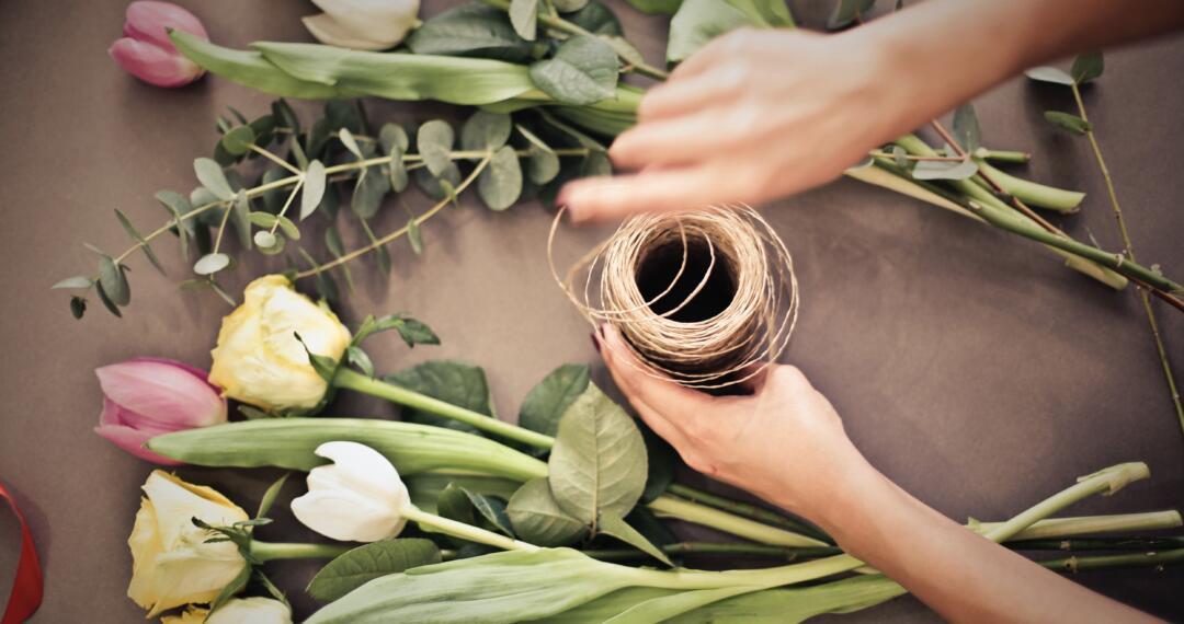 A florist's hand preparing flowers