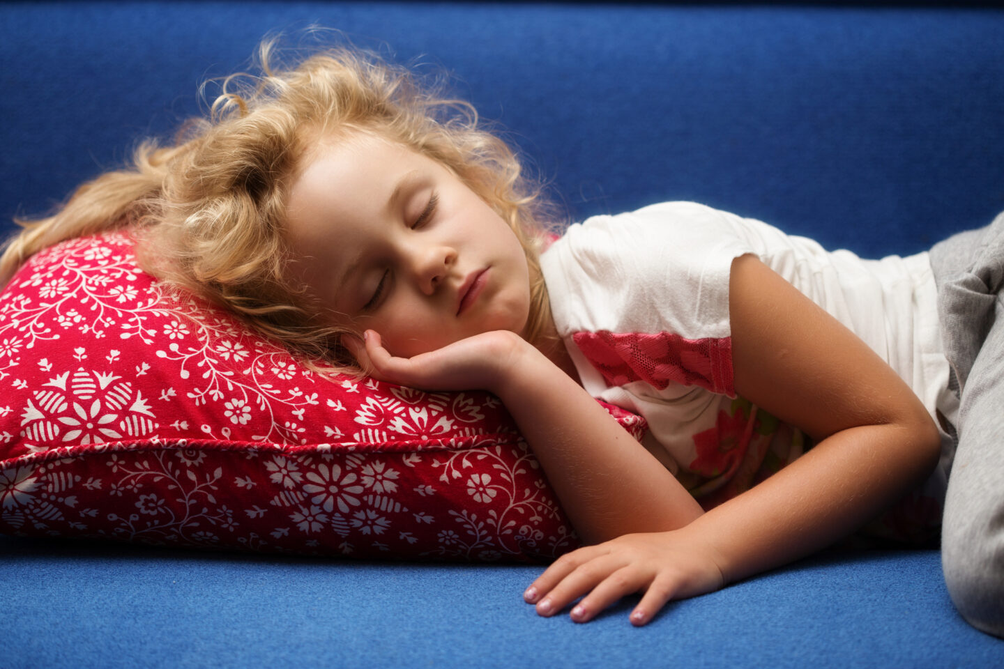 Little girl having a danger nap on a blue sofa with a red pillow