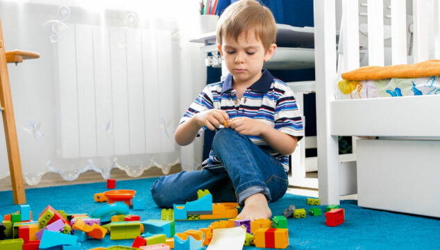 Child playing inside unsupervised in a room with blocks