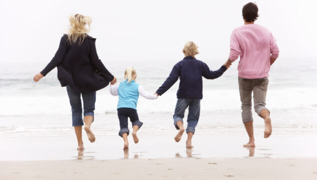 Family of four running hand in hand seen from behind bonding at the beach