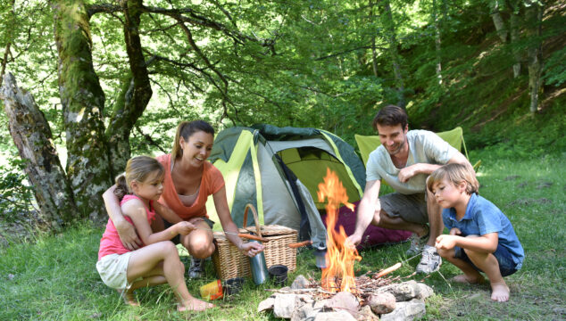 Two adults and two children around a camp fire, tent in the background,