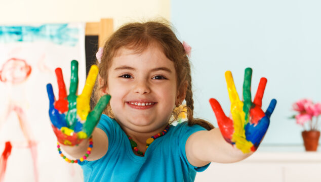young girl with her hands painted multiple colours