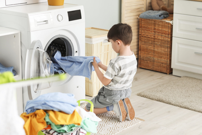 8 year old boy putting washing in machine